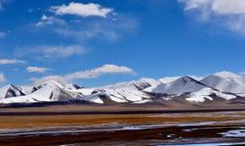 Viten för blå himmel fördunklar det tibetana snöberget fotografering för bildbyråer