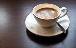 Vit kuper av kaffe på trä bordlägger Arkivfoton
