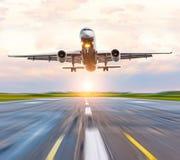 Vitesse d'atterrissage d'avion sur la piste à l'aéroport à l'aube de coucher du soleil Photo libre de droits