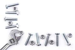 Viti, dadi e chiave su fondo bianco Fotografie Stock