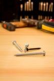 Viti e martello su una tavola Fotografia Stock
