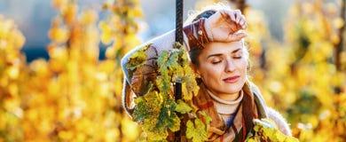 Viticultor relajado de la mujer que se coloca en viñedo al aire libre en otoño imagen de archivo