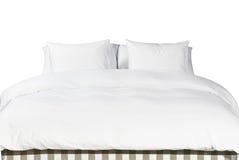 Vitkuddar och filt på en säng Royaltyfri Bild