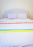 Vitkuddar på en säng Arkivfoto