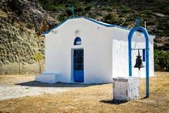 Vitkyrka med järnklockan i berg av den crete ön, Grekland Royaltyfria Bilder