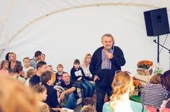 Vitkyrka, Ukraina, 16 September, 2017 Folket lyssnar till en person med en mikrofon Royaltyfri Foto
