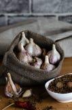 Vitlök i påsen med kryddor på trätabellen Royaltyfri Foto