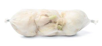 Vitlök i plast- netto förpacka på en vit isolerad bakgrund royaltyfri fotografi