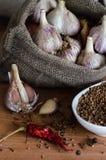 Vitlök med kryddor på trätabellen Arkivfoto