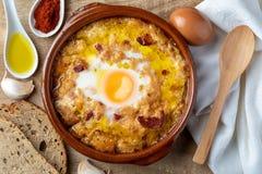Vitlök- och brödsoppaCastilian, från Spanien i lerakruka och dess huvudsakliga ingredienser ovanför sikt fotografering för bildbyråer
