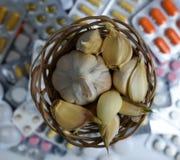 Vitlök och piller på vit bakgrund royaltyfri foto