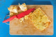 Vitlökbröd med den röda kniven på det hugga av kvarteret Royaltyfria Bilder