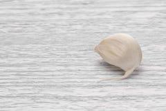 Vitlöksegment på en vit trätabell royaltyfri foto