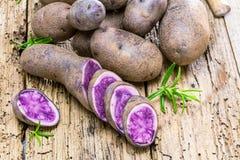 Vitolette noir eller purpurfärgad potatis På en trätabell fotografering för bildbyråer