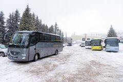 Buses on parking lot in the winter, Vitosha mountain, Bulgaria. Vitosha, Bulgaria - March 03, 2018: Multiple buses parked on snow covered parking in the Royalty Free Stock Photo