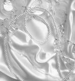 Vitpärlor och nacreous beeds på vit silke eller satäng som weddin Arkivfoton