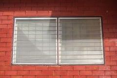 Vitrail sur le fond rouge de mur de briques photos stock