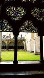 Vitral de la iglesia antigua que pasa por alto la hierba verde del patio Fotos de archivo libres de regalías