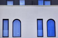 Vitraux bleus sur un mur moderne de bâtiment Images stock