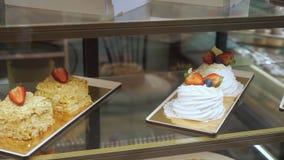 Vitrine da padaria com bolos e pastelarias nas prateleiras de vidro vídeos de arquivo