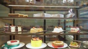 Vitrine de la panadería con las tortas y los pasteles en los estantes de cristal almacen de metraje de vídeo
