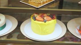 Vitrine de la panadería con las tortas y los pasteles en los estantes de cristal metrajes
