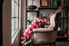 A vitrine from a flower shop with chair and flowers royalty free stock photos