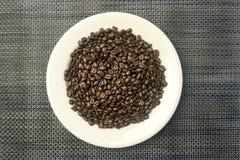 Vitrundaplatta med en hög av kaffebönor Arkivfoto