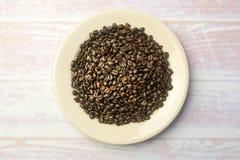 Vitrundaplatta med en hög av kaffebönor Royaltyfria Foton