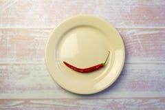 Vitrundaplatta med en röd peppar Arkivfoton