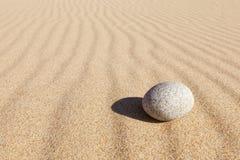 Vitrundasten som ligger på ren sand Begrepp av jämvikt, harmoni och meditationen minimalism royaltyfri foto