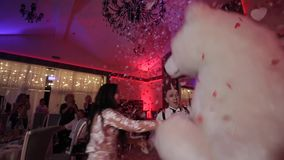 Vitryssland Minsk - Januari 15, 2019: Bröllopparti Mannen i en stor isbjörndräkt dansar på ett bröllop med bruden lager videofilmer