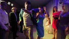 Vitryssland Minsk - Juli 26, 2018: Bröllopparti Koppla ihop dansen och går till och med kolonn av folk från två sidor folk lager videofilmer