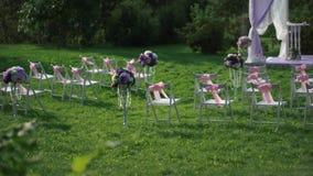 Vitstolar med rosa färgpilbågar och ett wdding altare i vit- och lavendelfärger stock video