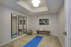 Vitt övningsrum med en bänk, en spegel och en genomköraretillbehör royaltyfri fotografi