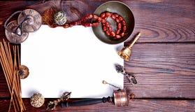 Vitt ark av papper bland musikaliska religiösa instrument Arkivbild