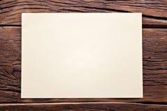 Vitt ark av papper på gammalt trä Arkivbild