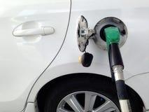 Vitt bilbränsleutfyllnadsgods på bränslestationen Bränsleutmatare på bensinstationen royaltyfri bild