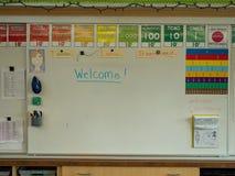 Vitt bräde för grundskolaklassrum med välkommet skriftligt royaltyfria foton