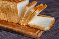 Vitt bröd som skivas med skivor på en träbakgrundsnärbild royaltyfria foton