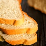 Vitt bröd som skivas på en mörk trätabell Selctive fokus Blurr Royaltyfria Bilder