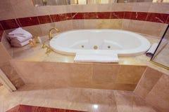 Vitt bubbelpoolbadkar som dekoreras med marmortegelplattor Royaltyfria Bilder
