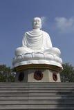 Vitt Buddhastatysammanträde i lotusblommablomma Arkivfoton