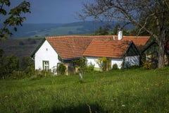 Vitt byhus med ett rött tak på ängarna av de vita Carpathiansna Royaltyfri Fotografi