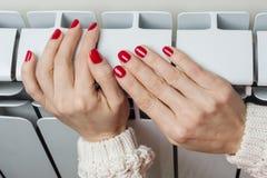 Vitt element för uppvärmning i lägenheten, kvinnlig hand på elementet royaltyfria bilder