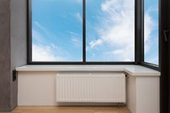 Vitt element för uppvärmning med regulatorn av värme i vardagsrum under ett stort fönster arkivbild