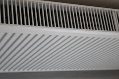 Vitt element Uppvärmningelement Nytt uppvärmningelement på en väggbakgrund arkivfoto