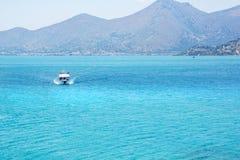 Vitt fartyg på det blåa vattnet nära bergen på Kreta Royaltyfri Bild