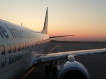 Vitt flygplan på en bakgrundssoluppgång arkivfoton