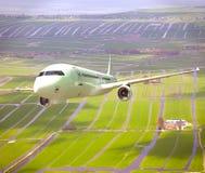 Vitt flygplan som 3D flyger ovannämnt landskap Arkivbild